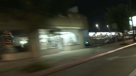 A-Car-Travels-Along-A-Street-At-Night-In-Studio-City-California-As-Seen-Through-The-Rear-Window-At-An-Angle
