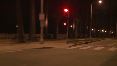 Un-Automóvil-Viaja-Por-Una-Calle-De-Noche-En-Santa-Mónica-California-Visto-A-Través-De-La-Ventana-Trasera-En-Un-ángulo-7