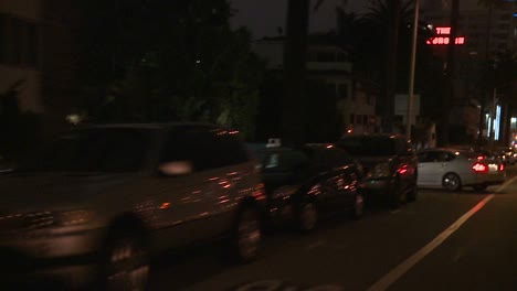 A-Car-Travels-Along-A-Street-At-Night-In-Los-Angeles-California-As-Seen-Through-The-Rear-Window-At-An-Angle-4
