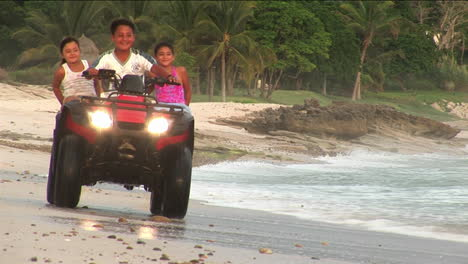 A-man-and-two-children-ride-an-ATV-through-the-water-on-a-beach