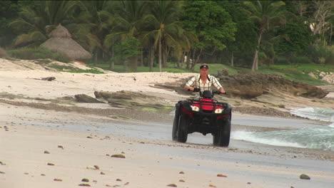 A-man-rides-an-ATV-through-the-water-on-a-beach-1