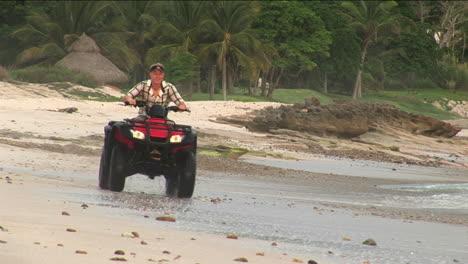 A-man-rides-an-ATV-through-the-water-on-the-beach
