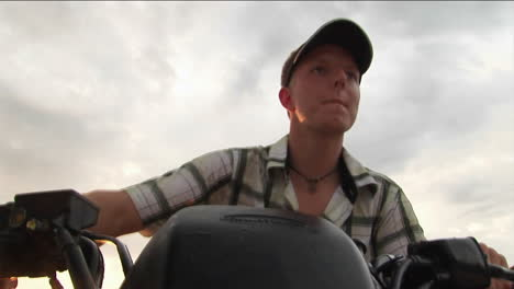 A-young-man-drives-an-ATV-with-an-overcast-sky-in-the-background