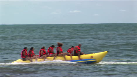 A-group-of-young-people-wearing-red-life-jackets-ride-through-the-water-on-a-yellow-boat