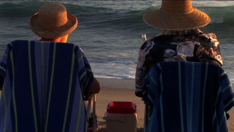 An-elderly-couple-makes-a-toast-to-the-ocean-waves-from-their-beach-chairs
