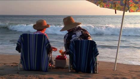 Una-Pareja-De-Ancianos-Comparte-Bebidas-Bajo-Una-Sombrilla-En-La-Playa-