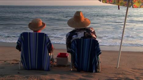 Una-Pareja-Se-Relaja-En-Sillas-De-Playa-Bajo-Una-Sombrilla-Mientras-Mira-El-Océano