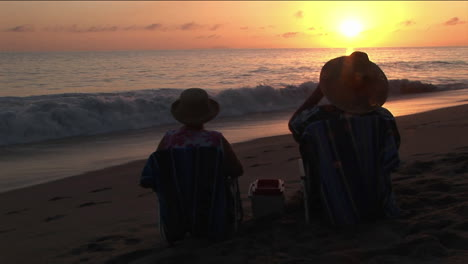 A-couple-toasts-the-ocean-from-their-beach-chairs