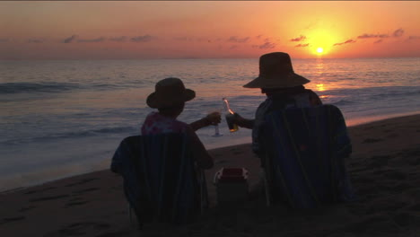 A-couple-toast-the-ocean-from-their-chairs-on-the-beach