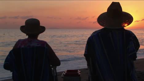Un-Par-Brinda-Por-El-Océano-Mientras-Se-Sientan-En-La-Playa