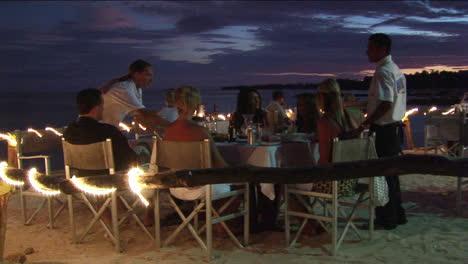 Los-Clientes-Cenan-En-Un-Restaurante-De-Playa-Al-Aire-Libre
