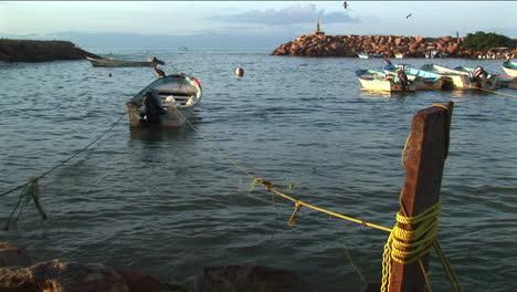 Un-Bote-A-Motor-Atado-A-Un-Muelle-Rocas-En-Las-Olas