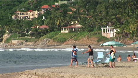 Three-people-walk-to-the-water-at-a-beach-resort