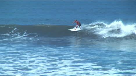 Un-Surfista-Recorre-El-Curso-De-Una-Ola-De-Superficie-Larga-Antes-De-Desaparecer