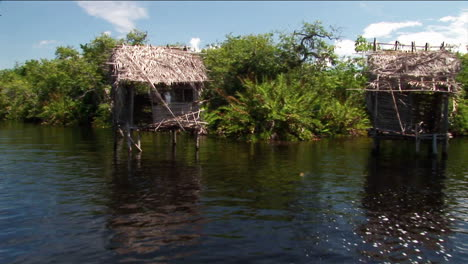 Thatchedroofed-homes-on-stilts-stand-in-a-tropical-river-area