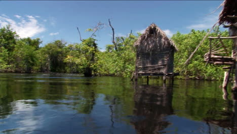 Thatchedroofed-homes-on-stilts-stand-in-a-tropical-river-area-1