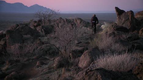Radfahrer-Fahren-Raue-Pfade-In-Einem-Wüstengebiet-In-Der-Nähe-Der-Dämmerung-Mit-Stirnlampen