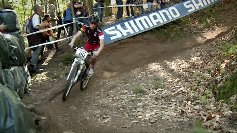 Bicyclists-race-in-the-woods-as-spectators-watch