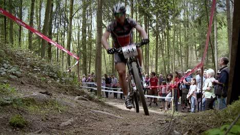 A-cyclist-races-up-a-rough-dirt-road-course