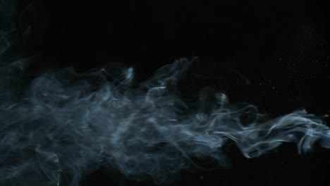 Cigarette-smoke-is-being-blown-in-against-a-black-background