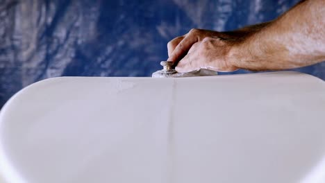 A-craftsman-is-planning-down-a-custom-surfboard