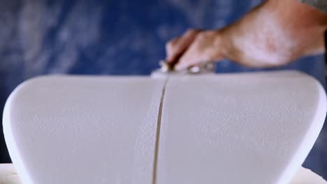 A-worker-is-shaving-and-cleaning-a-line-through-a-newly-manufactured-surfboard