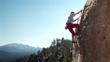 A-man-climbs-up-the-side-of-a-mountain