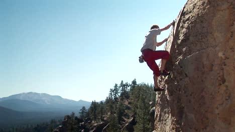 A-man-climbs-up-the-side-of-a-montaña