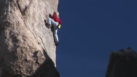 A-woman-climbs-up-the-side-of-a-mountain-1