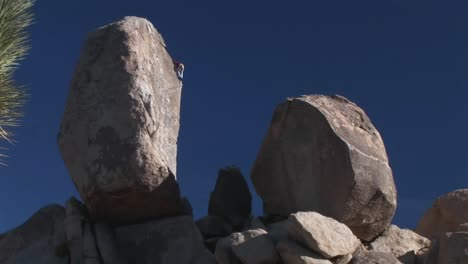 A-climber-begins-to-descend-a-rock-face