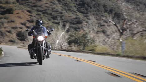 A-man-rides-a-motorcycle-down-a-mountain-road