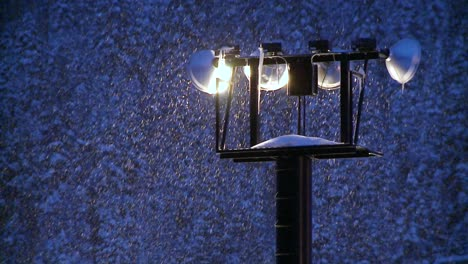 Snow-falls-at-night-through-beaming-floodlights