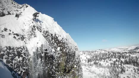 A-skier-jumps-off-the-side-of-a-mountain-and-another-person-sits-below