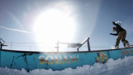 A-snowboarder-makes-a-slide-and-a-jump