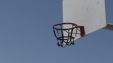A-man-dunks-a-basketball-and-hangs-on-the-rim-for-awhile