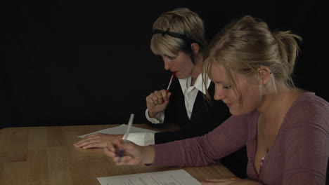 -women-sit-at-a-table-and-fill-out-paperwork