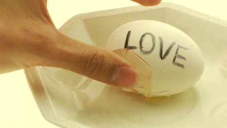 A-woman-s-hand-picks-up-a-hardboiled-egg-with-the-word-Love-written-on-it-and-cracks-it