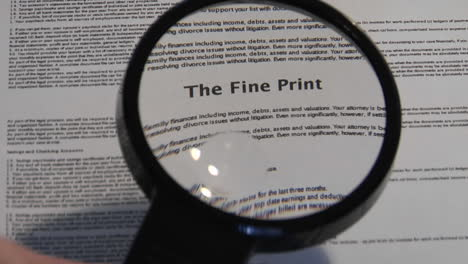 A-magnifying-glass-passes-over-a-paper-to-reveal-the-words-The-Fine-Print