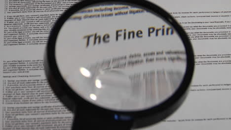 Magnifying-glass-passes-over-paper-to-reveal-the-words-The-Fine-Print