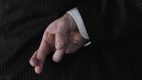 A-businessman-crosses-his-fingers-behind-his-back