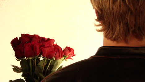 A-man-holds-flowers-in-his-hand-and-a-cleaver-behind-his-back