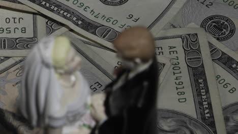 A-married-couple-figurine-stands-amid-twenty-dollar-bills