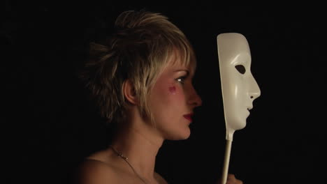 A-woman-with-a-heart-painted-on-her-cheek-holds-a-white-mask-up-to-her-face