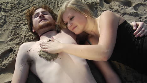 A-woman-packs-sand-on-a-mans-bare-chest-then-draws-a-heart-in-it-with-her-finger-while-they-lay-on-a-beach