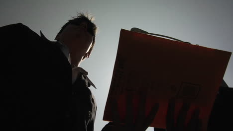 A-silhouetted-man-slyly-hands-another-silhouetted-man-an-envelope