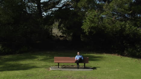 A-man-sits-on-a-park-bench-alone-with-a-flower