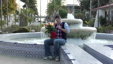 A-man-waits-excitedly-at-a-fountain-with-flowers-and-a-heartshaped-box