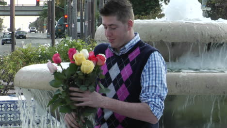 A-man-waits-excitedly-at-a-fountain-with-flowers-and-a-heartshaped-box-1