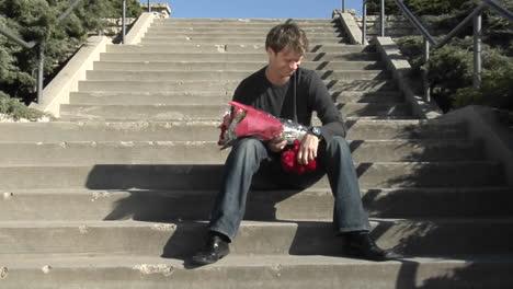 Un-Hombre-Espera-En-Las-Escaleras-Con-Flores-Y-Un-Osito-De-Peluche-
