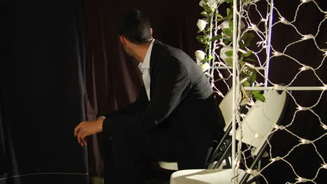 A-groom-sits-in-a-folding-chair-under-a-flower-arch